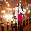 Fashionable lady wearing red dress and white coat outdoor in urban scenery with city lights in background. Full length portrait of young beautiful elegant woman posing in winter style. Street shot. — Stock fotografie #38589707