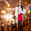 Fashionable lady wearing red dress and white coat outdoor in urban scenery with city lights in background. Full length portrait of young beautiful elegant woman posing in winter style. Street shot. — Stok fotoğraf #38589707