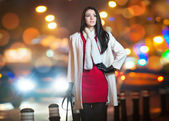 Fashionable lady wearing red dress and white coat outdoor in urban scenery with city lights in background. Full length portrait of young beautiful elegant woman posing in winter style. Street shot. — Stock Photo