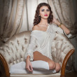 Beautiful young woman in white sitting on sofa posing provocatively in boudoir scenery. Attractive brunette girl with long hair and white long stockings laying down on vintage chair in bedroom — Stock Photo