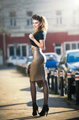 Attractive young woman in a urban fashion shot. Beautiful fashionable young girl with tight-fitting clothes and long legs posing on the street. Elegant blonde female posing in urban scenery — Stock Photo