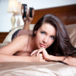 Beautiful and sexy brunette young woman wearing brown lingerie in bed. Fashion shoot lingerie indoor. Sexy young girl in black lingerie in a vintage scene — Stock Photo #38724959