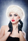 Attractive young Caucasian adult with black gloves isolated on grey background. Beautiful girl with red lips in white fur hat - studio isolated. Make up - beautiful female art portrait studio isolated — Stock Photo