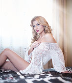 Young beautiful sexy woman in white lingerie posing challenging indoor staying on bed. Attractive sexy blonde wearing lace lingerie. Portrait of sensual long fair hair woman in classic scene. — Stock Photo