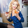 Attractive sexy blonde female with bright blue blouse and black stockings posing smiling eating a pizza slice and holding a glass with red wine. Portrait of sensual fair hair woman in modern scenery. — Stock Photo #38880829