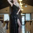 Young beautiful luxurious woman in long elegant black dress. Beautiful young blonde woman with bright lights in background. Seductive blonde woman in luxury manor, vintage style — Stock Photo #39052577