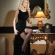 Young beautiful luxurious woman in long elegant black dress. Beautiful young blonde woman with bright lights in background. Seductive blonde woman in luxury manor, vintage style — Stock Photo #39052603