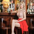 Attractive blonde woman with long hair in elegant nude and red dress sitting on bar stool. Gorgeous blonde model showing her long legs with high heels posing provocatively in vintage bar — Stock Photo