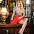 Attractive blonde woman with long hair in elegant nude and red dress sitting on bar stool. Gorgeous blonde model showing her long legs with high heels posing provocatively in vintage bar — Stock Photo #39052643