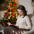 Beautiful sexy woman with Xmas tree in background reading a book sitting on chair. Portrait of a woman reading a book sitting comfortable with a blanket on legs. Attractive brunette female relaxing. — Stock Photo #39262817