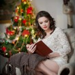 Beautiful sexy woman with Xmas tree in background reading a book sitting on chair. Portrait of a woman reading a book sitting comfortable with a blanket on legs. Attractive brunette female relaxing. — Stock Photo #39262839