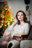 Beautiful sexy woman with Xmas tree in background reading a book sitting on chair. Portrait of a woman reading a book sitting comfortable with a blanket on legs. Attractive brunette female relaxing. — Stock Photo