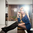 Attractive sexy blonde female with bright blue blouse and black stockings posing smiling holding a glass with red wine. Portrait of sensual fair hair woman and long legs in modern kitchen — Stock Photo