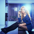 Attractive sexy blonde female with bright blue blouse and black stockings posing smiling holding a glass with red wine. Portrait of sensual fair hair woman and long legs in modern kitchen — Stock Photo #39332689