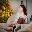 Beautiful sexy woman with Xmas tree in background reading a book sitting on chair. Portrait of a woman reading a book sitting comfortable. Attractive brunette female relaxing. — Stock Photo #39340811
