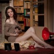 Beautiful sexy woman near a red gramophone surrounded by photo frames in vintage scenery. Portrait of girl in slim fit short dress posing comfortable in cosy scenery. Attractive brunette female. — Stock Photo
