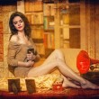 Beautiful sexy woman near a red gramophone surrounded by photo frames in vintage scenery. Portrait of girl in slim fit short dress posing comfortable in cosy scenery. Attractive brunette female. — Stock Photo #39401033