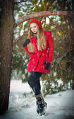 Attractive blonde girl with gloves, red coat and red hat posing winter snow.Beauty woman in the winter scenery.Young woman in wintertime outdoor — Stock Photo