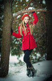 Attractive blonde girl with gloves, red coat and red hat posing in winter snow. Beautiful woman in the winter scenery. Young woman in wintertime outdoor — Stock Photo