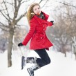 Attractive blonde girl with gloves, red coat and red hat posing in winter snow. Beautiful woman in the winter scenery. Young woman in wintertime outdoor — Foto de Stock