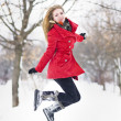 Attractive blonde girl with gloves, red coat and red hat posing in winter snow. Beautiful woman in the winter scenery. Young woman in wintertime outdoor — Stock fotografie