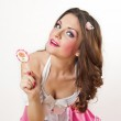 Attractive girl with a lollipop in her hand and pink dress isolated on white. Beautiful long hair brunette playing with a lollipop. Studio shot. Young woman with dynamic look posing pretty — Stock Photo #39544067