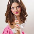 Attractive girl with a lollipop in her hand and pink dress isolated on white. Beautiful long hair brunette playing with a lollipop. Studio shot. Young woman with dynamic look posing pretty — Stock Photo