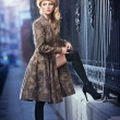 Attractive elegant blonde young woman wearing an outfit with Russian influence in urban fashion shot. Beautiful fashionable young girl with long legs and fur cap posing on street — Stock Photo