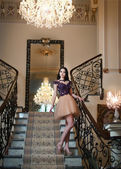 The beautiful girl in a short black and nude dress posing in a vintage scene. Young beautiful woman wearing a lace dress in an old hotel. Sensual elegant young woman in black short dress indoor shot. — Stock Photo