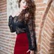 Charming young brunette womin black lace blouse, red skirt and high heels near brick wall. Sexy gorgeous young womnear old wall. Full length portrait of sensual womwith long hair — Stock Photo #40030925