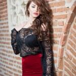 charmante jeune femme brune à chemisier de dentelle noire, jupe rouge et des talons hauts, près du mur de brique. sexy superbe jeune femme près de vieux mur. portrait de toute la longueur d'une femme sensuelle avec de longs cheveux — Photo #40030929