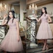 Beautiful long hair girl in nude colored dress posing in a vintage scene. Young beautiful woman wearing a lace dress in luxury scenery on stairs. Sensual elegant young woman in nude dress indoor shot. — Stock Photo #40450957