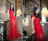The beautiful girl in a long red dress posing in a vintage scene. Young beautiful woman wearing a red dress in luxury scenery. Sensual elegant young woman in red long dress indoor shot. — Stock Photo