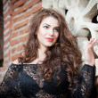 Charming young brunette woman in black lace blouse near a red brick wall. Sexy gorgeous young woman with long curly hair near old wall. Beautiful portrait of a sensual woman with long hair — Stock Photo #40711925