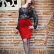 Charming young brunette womin black lace blouse, red skirt and high heels near brick wall. Sexy gorgeous young womnear old wall. Full length portrait of sensual womwith long hair — Foto Stock #40711907