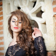 Charming young brunette womin black lace blouse near red brick wall. Sexy gorgeous young womwith long curly hair near old wall. Beautiful portrait of sensual womwith long hair — Stockfoto #40711909