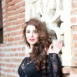 Stock Photo: Charming young brunette womin black lace blouse near red brick wall. Sexy gorgeous young womwith long curly hair near old wall. Beautiful portrait of sensual womwith long hair
