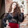 Charming young brunette womin black lace blouse, red skirt and high heels near brick wall. Sexy gorgeous young womnear old wall. Full length portrait of sensual womwith long hair — Foto Stock #40711915