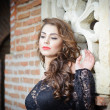 Stock Photo: Charming young brunette woman in black lace blouse near a red brick wall. Sexy gorgeous young woman with long curly hair near old wall. Beautiful portrait of a sensual woman with long hair