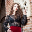 Charming young brunette woman in black lace blouse, red skirt and high heels near the brick wall. Sexy gorgeous young woman near old wall. Full length portrait of a sensual woman with long hair — Stock Photo #40711921