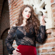 Charming young brunette womin black lace blouse, red skirt and high heels near brick wall. Sexy gorgeous young womnear old wall. Full length portrait of sensual womwith long hair — Stock fotografie #40711921
