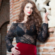 Charming young brunette womin black lace blouse, red skirt and high heels near brick wall. Sexy gorgeous young womnear old wall. Full length portrait of sensual womwith long hair — Stok Fotoğraf #40711927