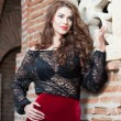 Stockfoto: Charming young brunette womin black lace blouse, red skirt and high heels near brick wall. Sexy gorgeous young womnear old wall. Full length portrait of sensual womwith long hair