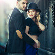 Couple in love in railway station. Beautiful well-dressed couple standing on railway platform. Handsome brunette young man holding a fashionable blonde with hat next to a train — Stock Photo