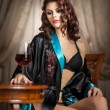 Beautiful sexy woman with glass of wine sitting on chair. Portrait of a woman with long curly hair posing challenging. Sexy brunette sitting near wood table with glass with red wine in vintage scene — Stock Photo #40895507