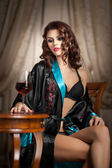 Beautiful sexy woman with glass of wine sitting on chair. Portrait of a woman with long curly hair posing challenging. Sexy brunette sitting near wood table with glass with red wine in vintage scene — Stock Photo