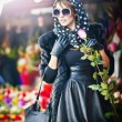 Beautiful brunette woman with gloves choosing flowers at the florist shop. Fashionable female with sunglasses and head scarf at flower shop. Pretty brunette in black choosing flowers - urban shot — Stock Photo #40920025