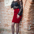 Charming young brunette womin black lace blouse, red skirt and high heels near brick wall. Sexy gorgeous young womnear old wall. Full length portrait of sensual womwith long curly hair — Stockfoto #40987631