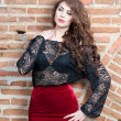 Charming young brunette womin black lace blouse, red skirt and high heels near brick wall. Sexy gorgeous young womnear old wall. Full length portrait of sensual womwith long curly hair — Stock fotografie #40987637