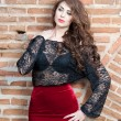 Charming young brunette womin black lace blouse, red skirt and high heels near brick wall. Sexy gorgeous young womnear old wall. Full length portrait of sensual womwith long curly hair — Stockfoto #40987637